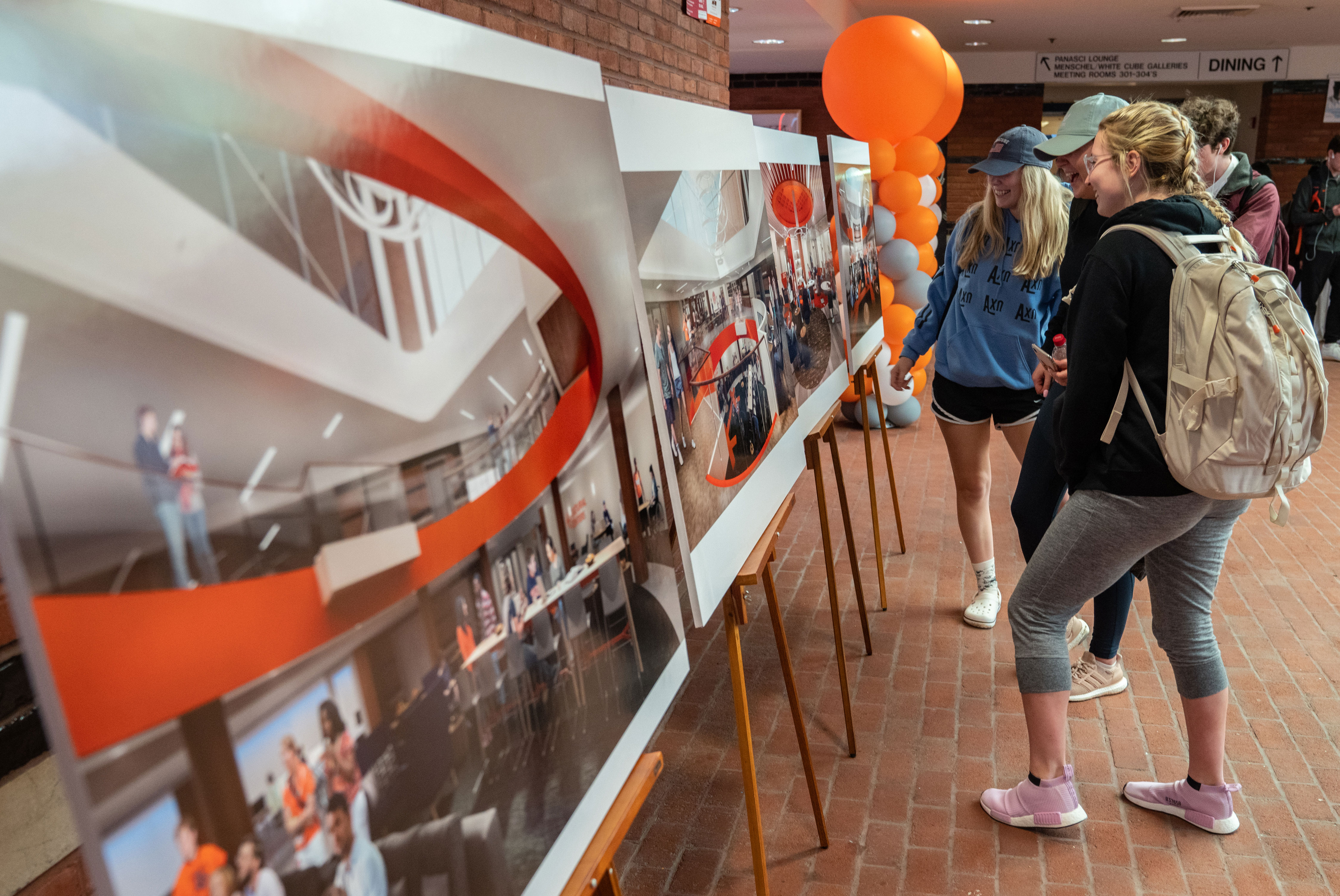 Students looking at the renderings of the renovated Schine Student Center.
