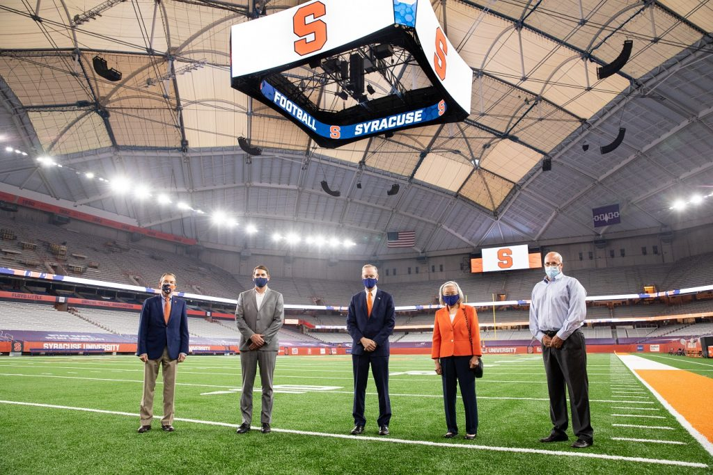 John Wildhack, director of Athletics; Syracuse Mayor Ben Walsh; Chancellor Kent Syverud; Ruth Chen, professor of practice in the College of Engineering and Computer Science; Pete Sala, chief facilities officer pose inside the renovated Stadium